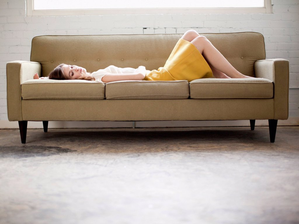 Young woman lying on sofa : Stock Photo