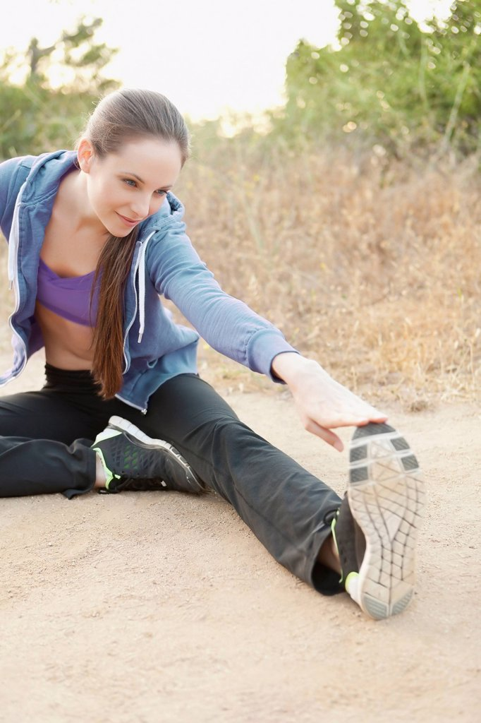 Stock Photo: 1795R-70606 Woman exercising on dusty track
