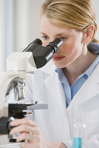 Stock Photo: 1795R-7096 Female scientist looking into microscope