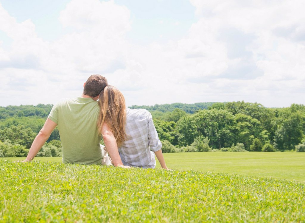 Stock Photo: 1795R-71147 Couple sitting on grass and looking at view
