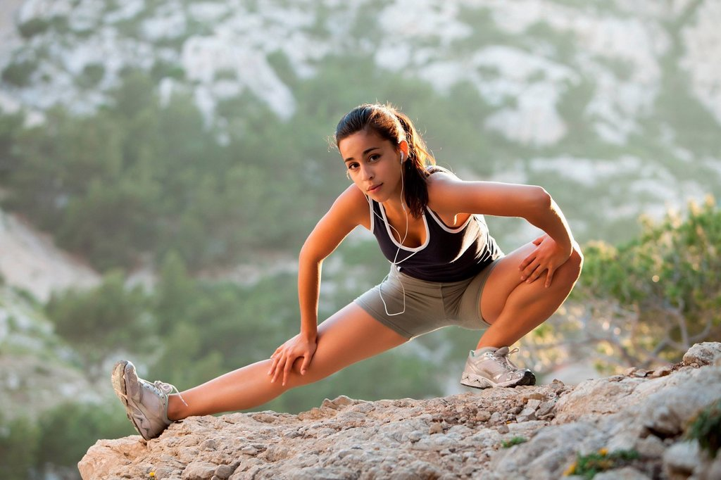 Stock Photo: 1795R-71288 France, Marseille, Young woman stretching on cliff