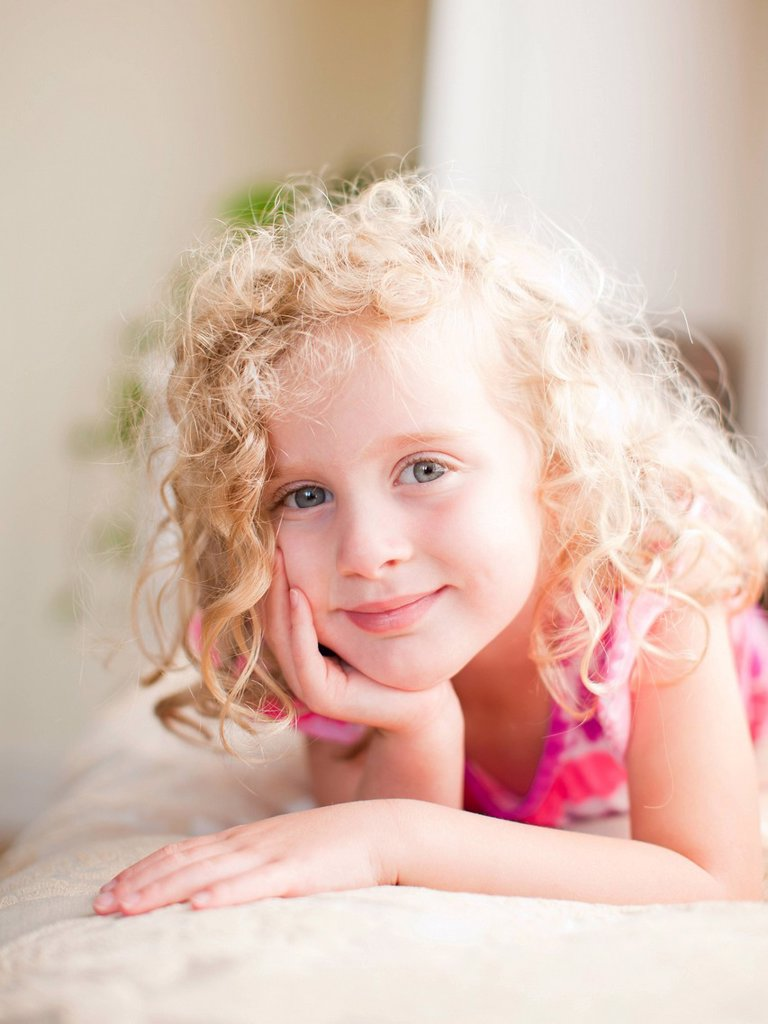 Stock Photo: 1795R-71456 Portrait of girl 4_5 lying on bed