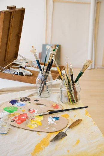 Artist's palette and paintbrushes on table : Stock Photo