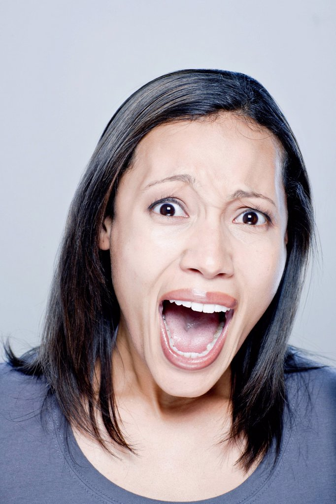 Portrait of screaming young woman, studio shot : Stock Photo