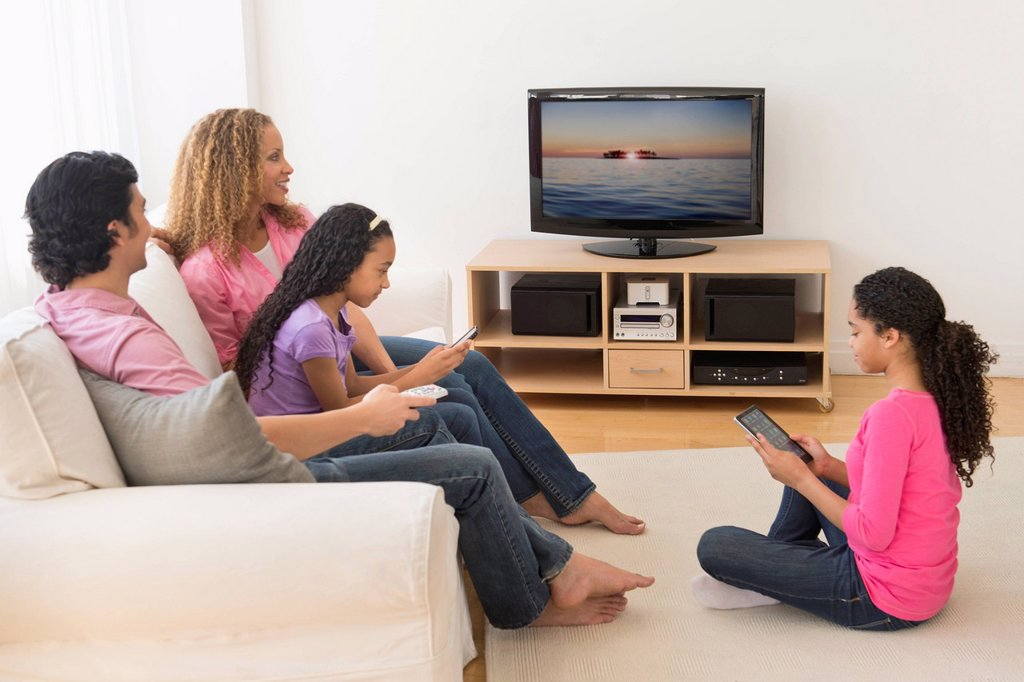 Stock Photo: 1795R-72184 Parents with daughters 10_13 watching tv