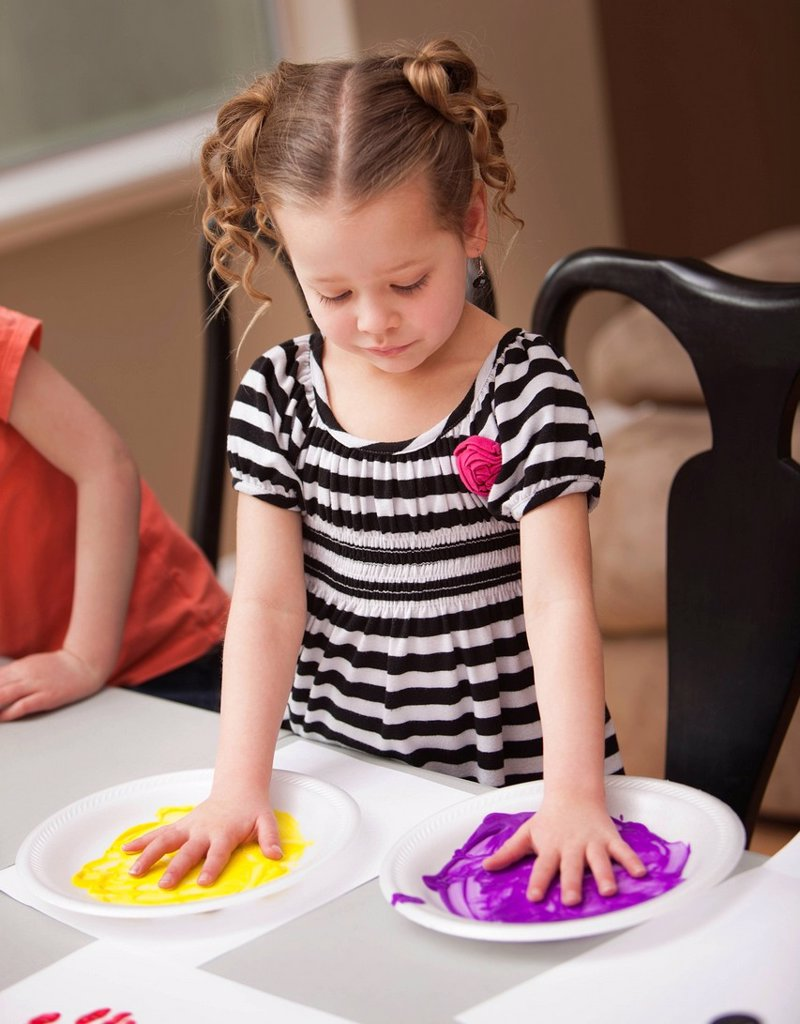 Girl 4_5 holding her hands on plates with paint : Stock Photo