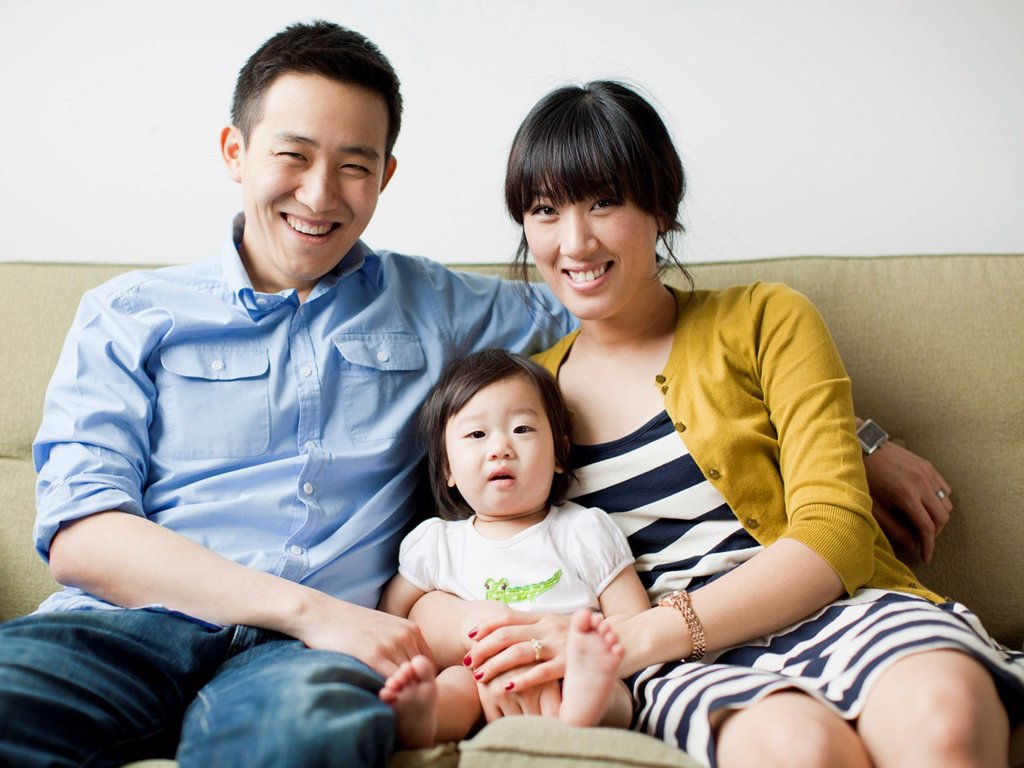Stock Photo: 1795R-73638 Portrait of young parents with baby girl 12_17 months