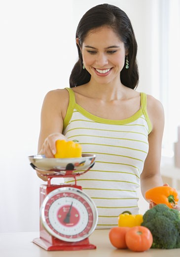 Woman weighing vegetables in kitchen : Stock Photo