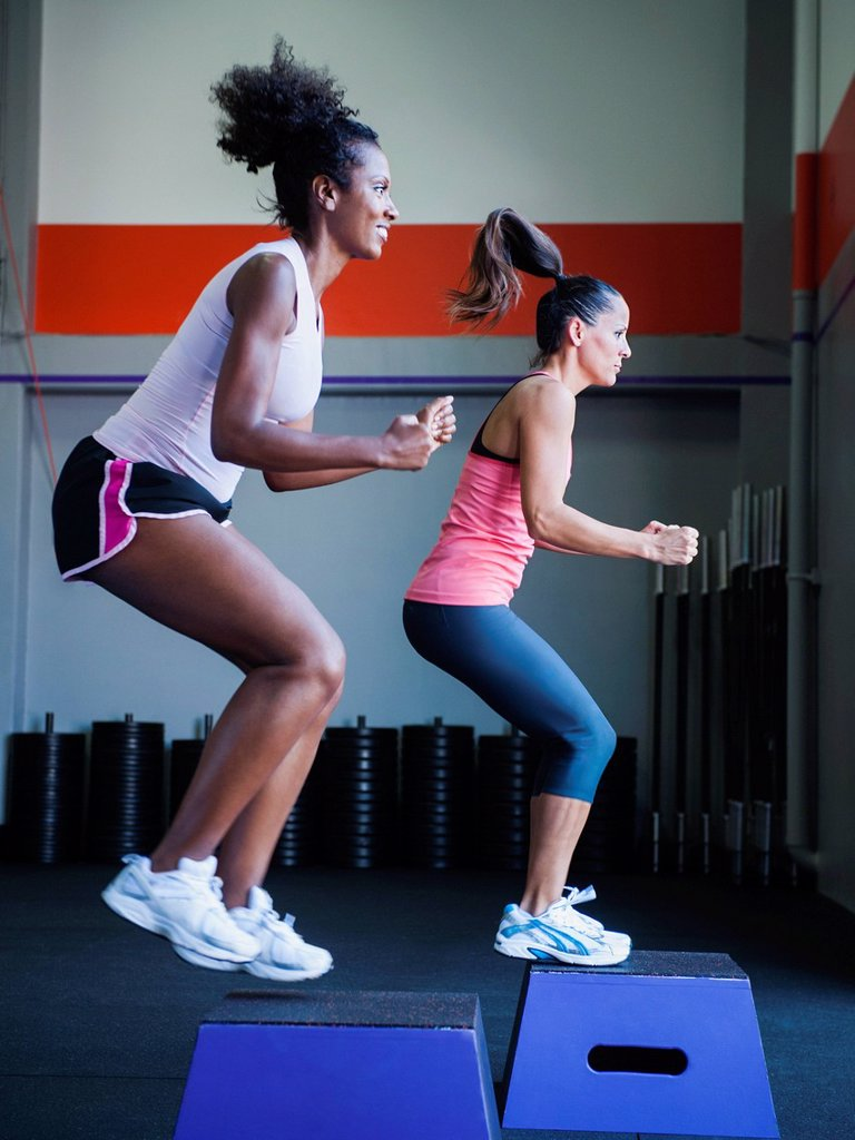 Stock Photo: 1795R-75881 Two women in step aerobics class