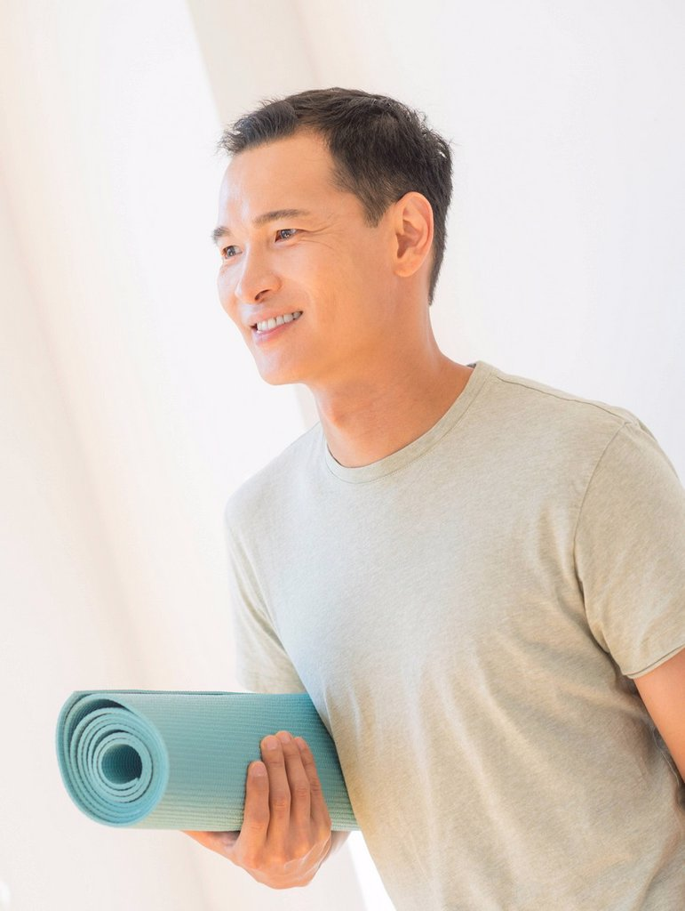 Happy mid adult man holding exercising mat : Stock Photo