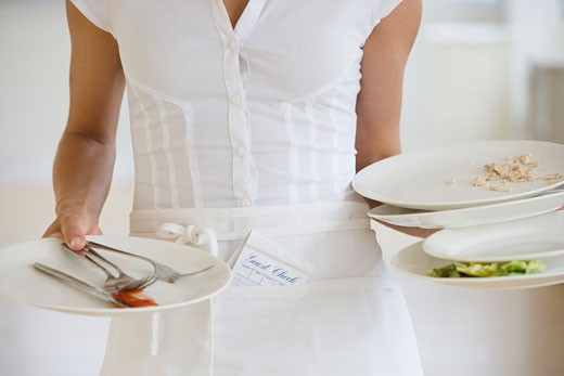 Stock Photo: 1795R-7659 Waitress holding dirty plates