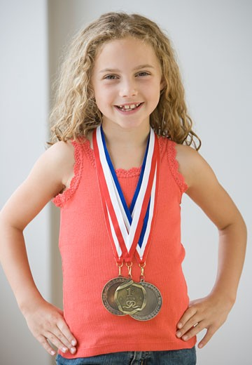 Girl wearing medals around neck : Stock Photo
