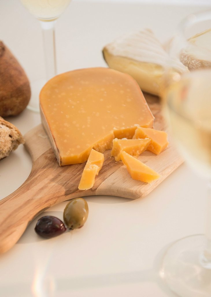 Studio shot of cheese on chopping board : Stock Photo
