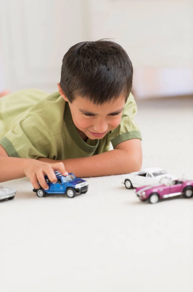 Portrait of boy 6_7 playing with toy cars : Stock Photo
