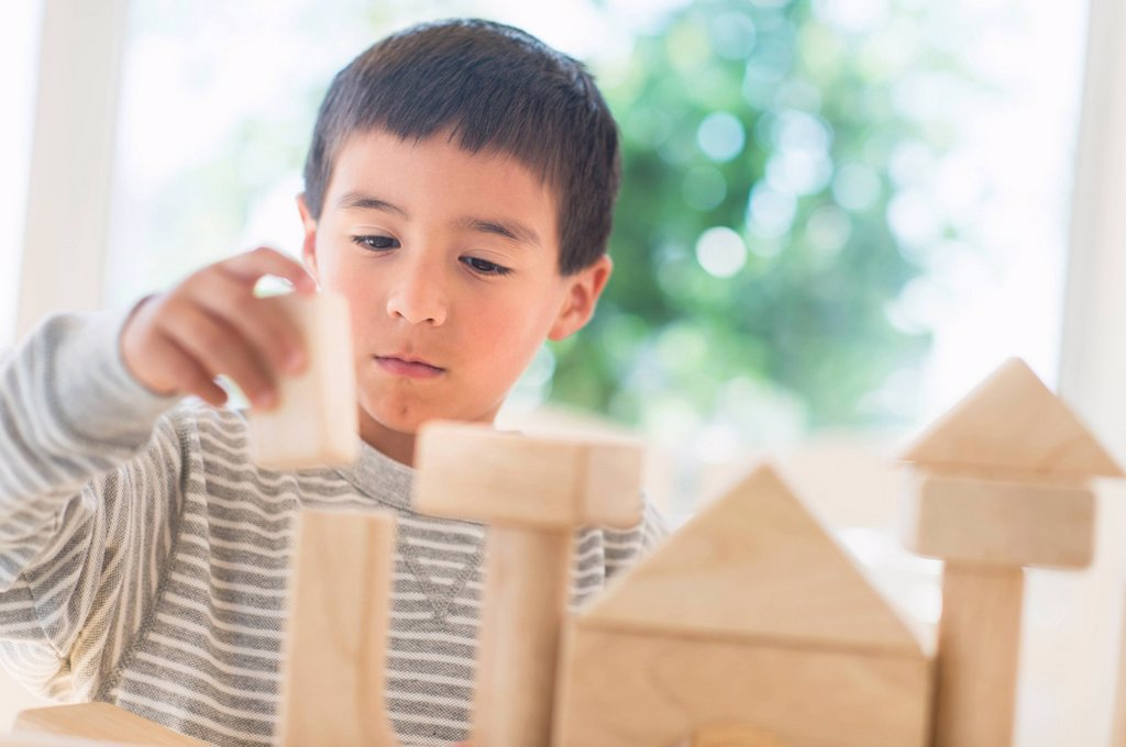 Boy 6_7 playing with toy blocks : Stock Photo