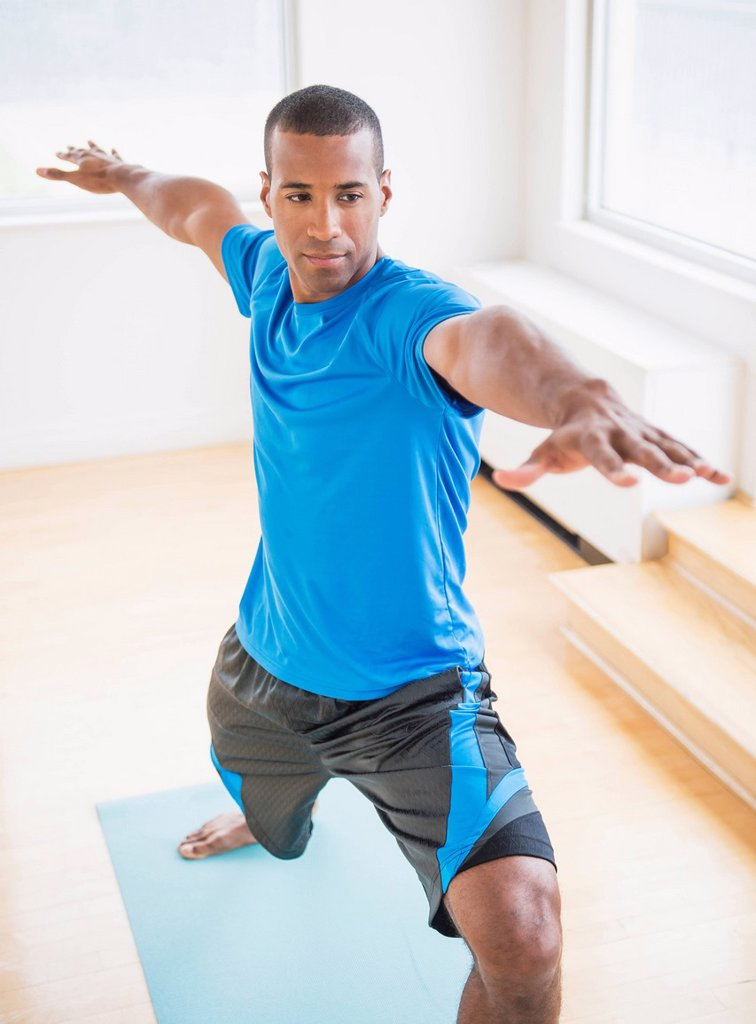 Young man practicing yoga : Stock Photo