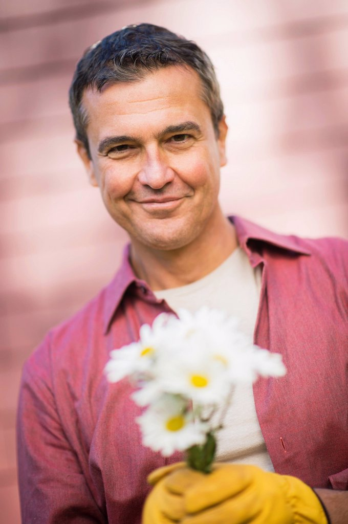 Stock Photo: 1795R-77992 Portrait of smiling man holding flowers
