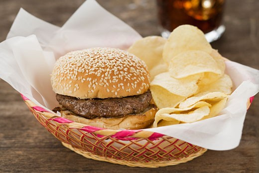 Hamburger and chips in basket : Stock Photo