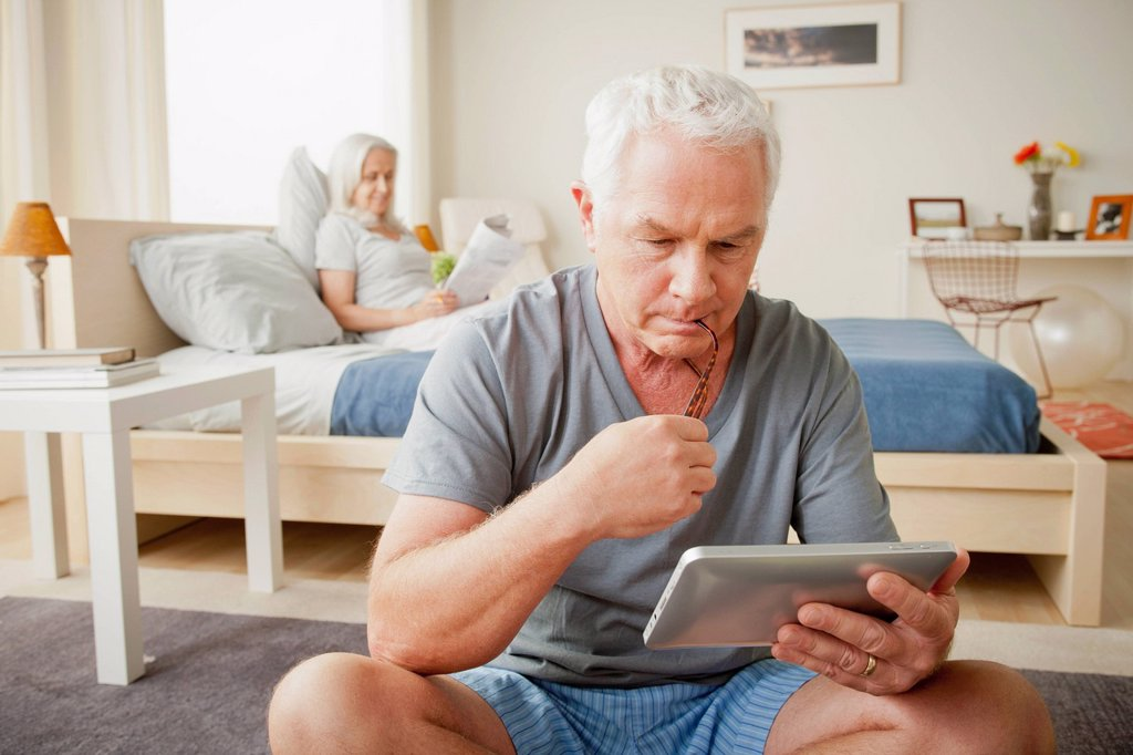 Senior man holding photo frame, woman sitting on bed in background : Stock Photo