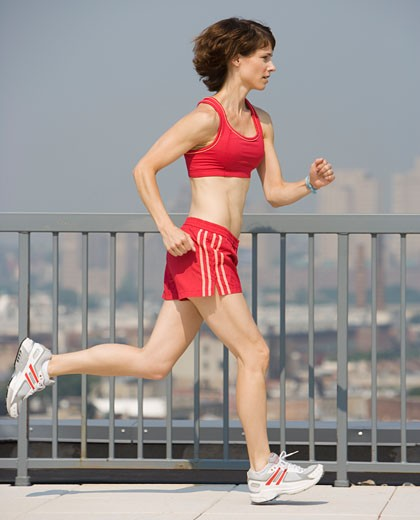 Stock Photo: 1795R-7830 Woman jogging on urban sidewalk
