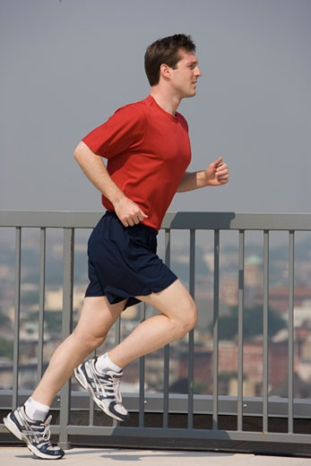 Stock Photo: 1795R-7831 Man jogging on urban sidewalk