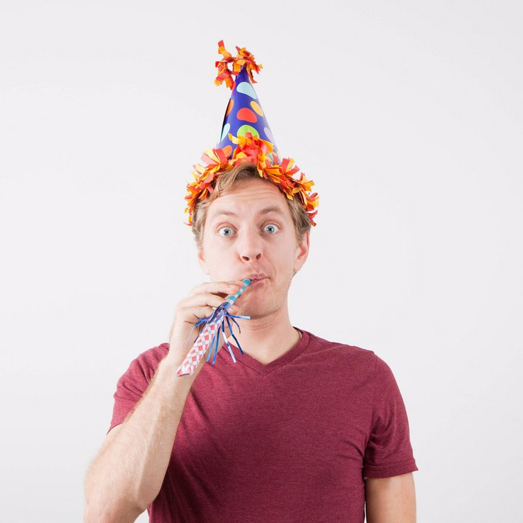 Stock Photo: 1795R-78625 Man with party hat and party horn blower