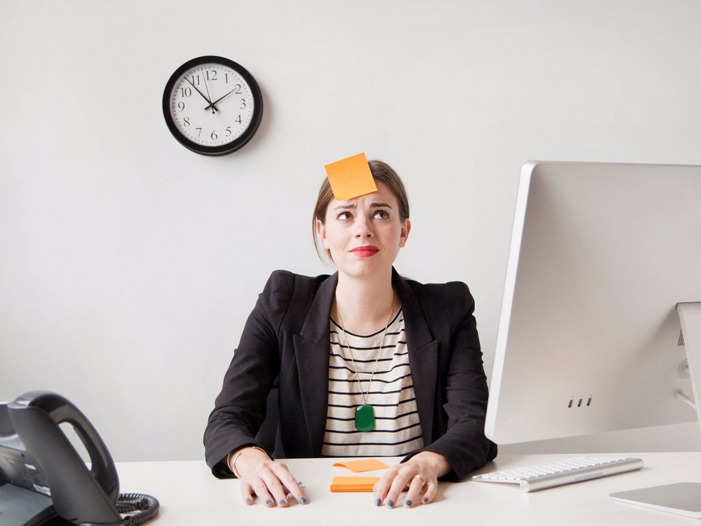 Stock Photo: 1795R-78982 Studio shot of young woman working in office with adhesive note on her forehead