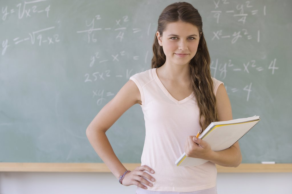Girl standing in front of blackboard : Stock Photo