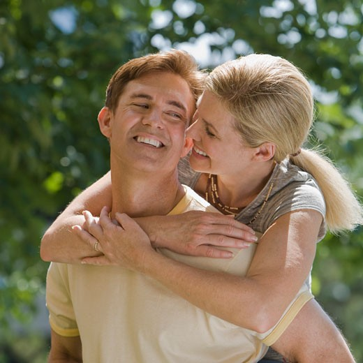 Stock Photo: 1795R-8092 Man giving wife piggyback ride