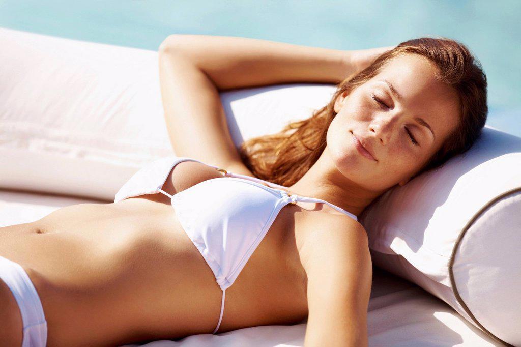 Stock Photo: 1795R-82569 Young woman in bikini resting at swimming pool
