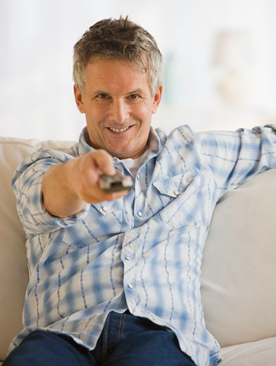 Man pointing television remote control : Stock Photo