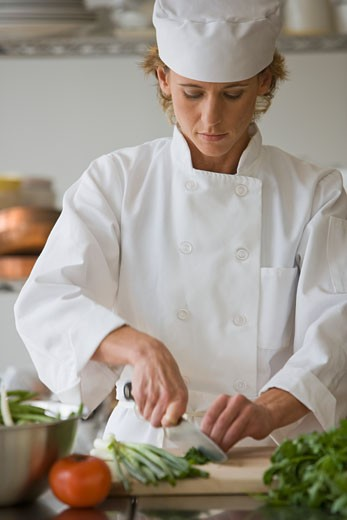 Female chef chopping vegetables : Stock Photo