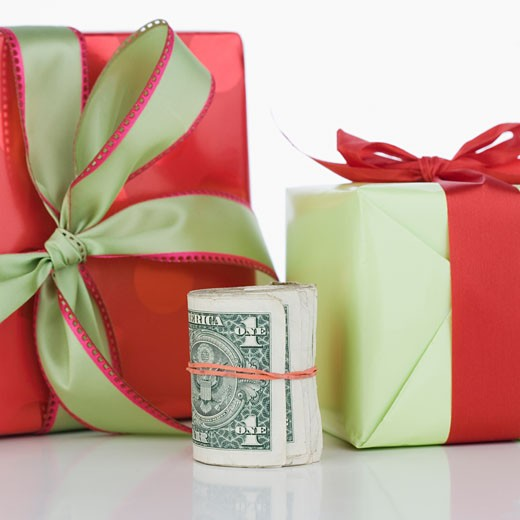 Studio shot of roll of dollar bills and gifts : Stock Photo