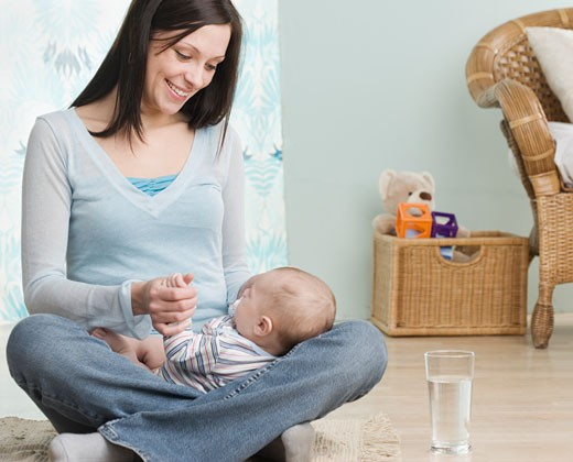 Mother holding baby on her lap : Stock Photo
