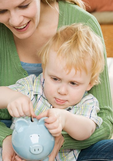 Mother and young son putting change in piggy bank : Stock Photo