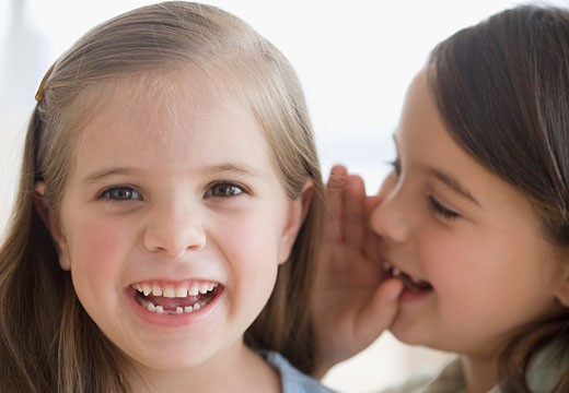 Close up of sisters telling secret : Stock Photo