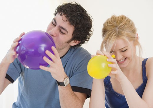 Stock Photo: 1795R-9885 Couple blowing up balloons