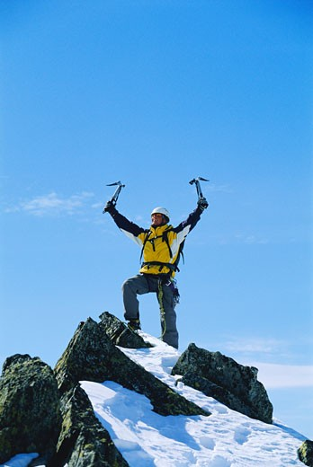 Mountain climber standing on snowy mountain victorious and smiling : Stock Photo