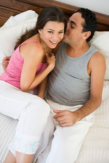Stock Photo: 1799R-13715 Couple relaxing on bed in bedroom snuggling and smiling (selective focus)