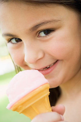 Stock Photo: 1799R-13818 Young girl outdoors eating ice cream and smiling (selective focus)