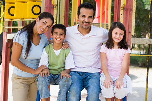 Family sitting on playground structure smiling (selective focus) : Stock Photo