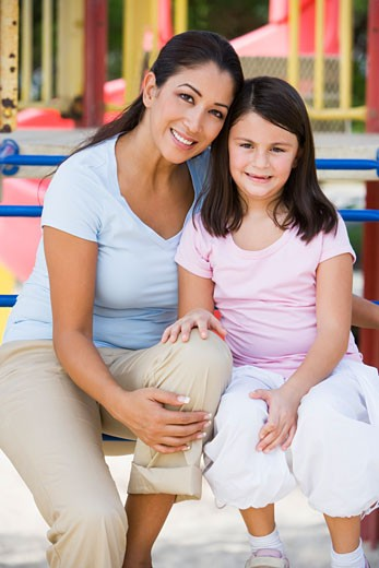 Mother and daughter girl sitting on playground structure smiling (selective focus) : Stock Photo