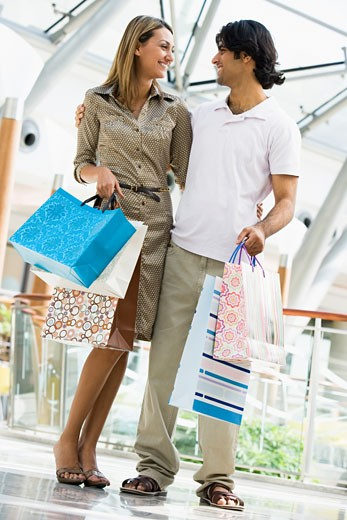 Stock Photo: 1799R-13925 Couple standing in mall smiling (selective focus)