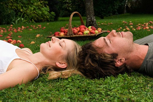 Side profile of a young couple sleeping on the grass in a garden : Stock Photo