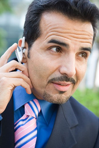 Stock Photo: 1799R-20654 Businessman outdoors wearing headset (selective focus)