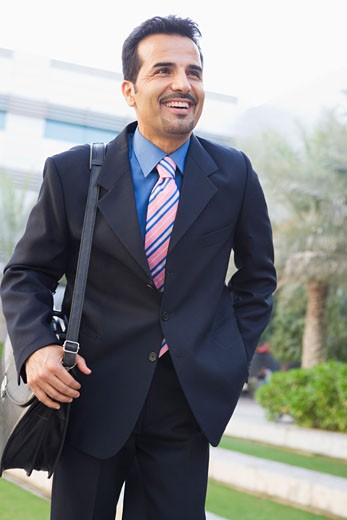 Stock Photo: 1799R-20660 Businessman walking outdoors smiling (high key/selective focus)
