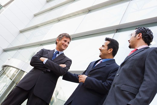 Three businessmen standing outdoors by building talking and smiling (high key/selective focus) : Stock Photo