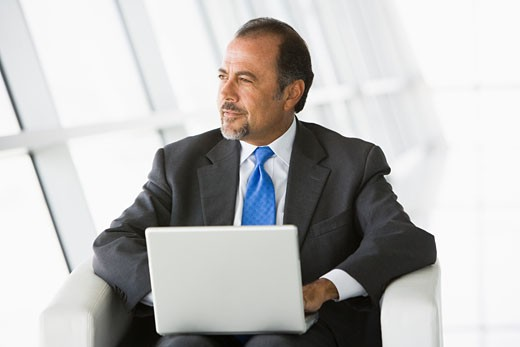 Stock Photo: 1799R-20741 Businessman sitting indoors with laptop looking out window (high key/selective focus)