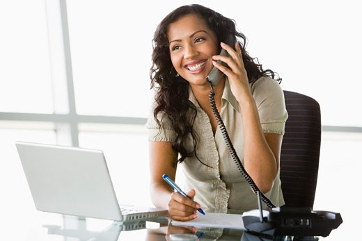 Stock Photo: 1799R-20760 Businesswoman in office on telephone by laptop smiling (high key/selective focus)