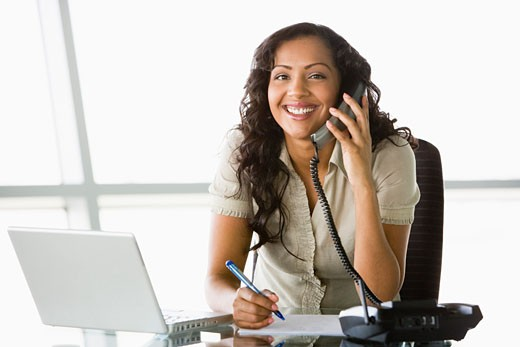 Businesswoman in office on telephone by laptop smiling (high key/selective focus) : Stock Photo